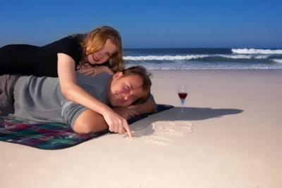 Młoda para - kobieta i mężczyzna - leżą na plaży. Kobieta leży na plecach mężczyzny i pisze palcem po piasku.