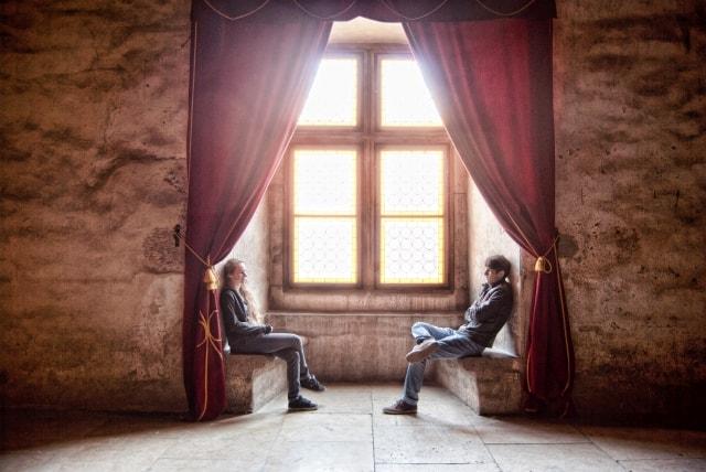 Para siedzi na przeciw siebie przy oknie