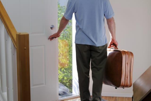 Mężczyzna niosący walizkę otwierający frontowe drzwi swojego domu aby wyjść