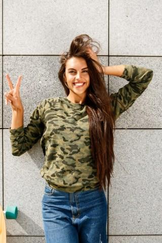 Szczęśliwa, uśmiechnięta kobieta pokazuje znak zwycięstwa