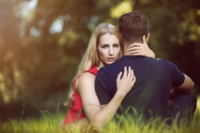 Para zakochanych, mężczyzna siedzi tyłem, kobieta przodem i go obejmuje