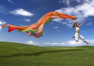 Kobieta skacząca z kolorową szarfą