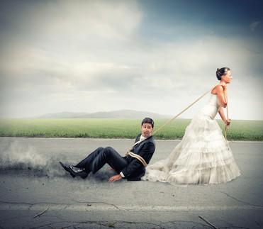 Kobieta w sukni ślubnej ciągnie za sobą związanego narzeczonego