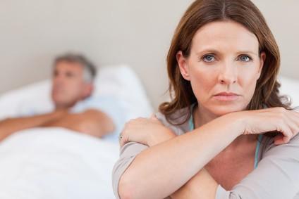 Smutna kobieta siedzi na łóżku, w tle leży jej mąż