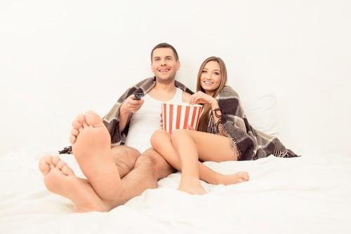 Kobieta i mężczyzna w łóżku oglądają film