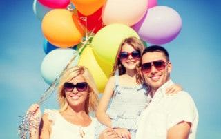 Uśmiechnięci rodzice z dzieckiem na rękach taty z kolorowymi balonami